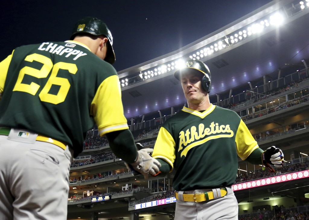 Oakland Athletics' Mark Canha, right, is congratulated by teammate Matt Chapman (26) after scoring on a single by Jonathan Lucroy against the Minnesot...