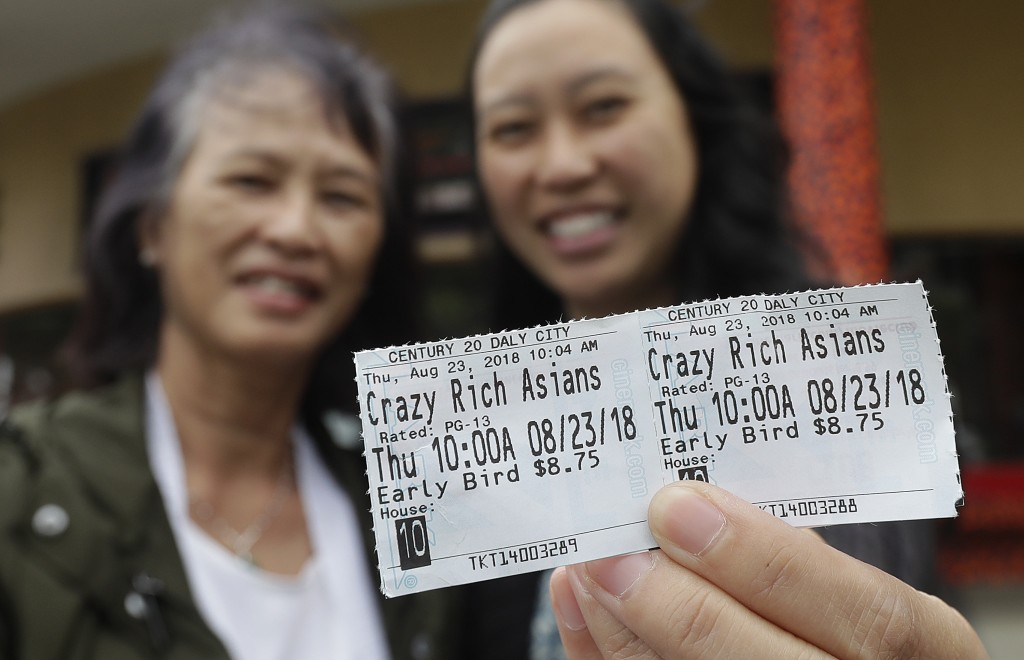In this Thursday, Aug. 23, 2018 photo, Audrey Sue-Matsumoto, right, holds tickets as she poses for photos with her mother Alice Sue while interviewed ...