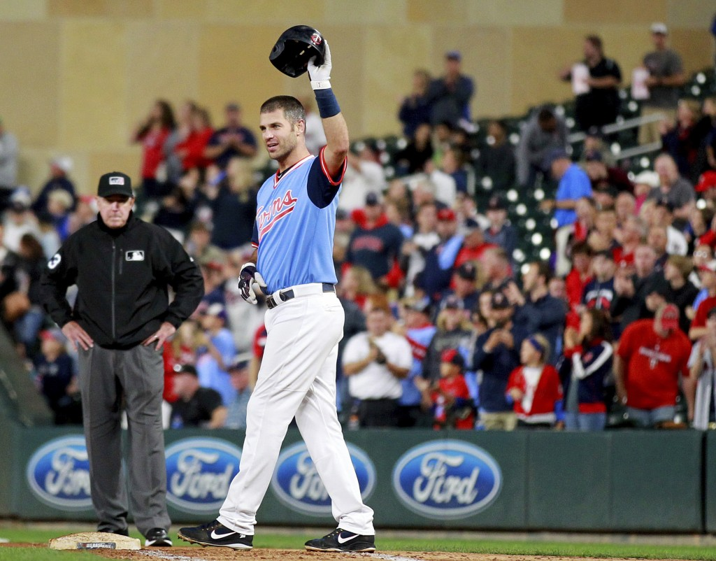 Minnesota Twins' Joe Mauer salutes the crowd after hitting a single against the Oakland Athletics in the fifth inning during a baseball game Friday, A...