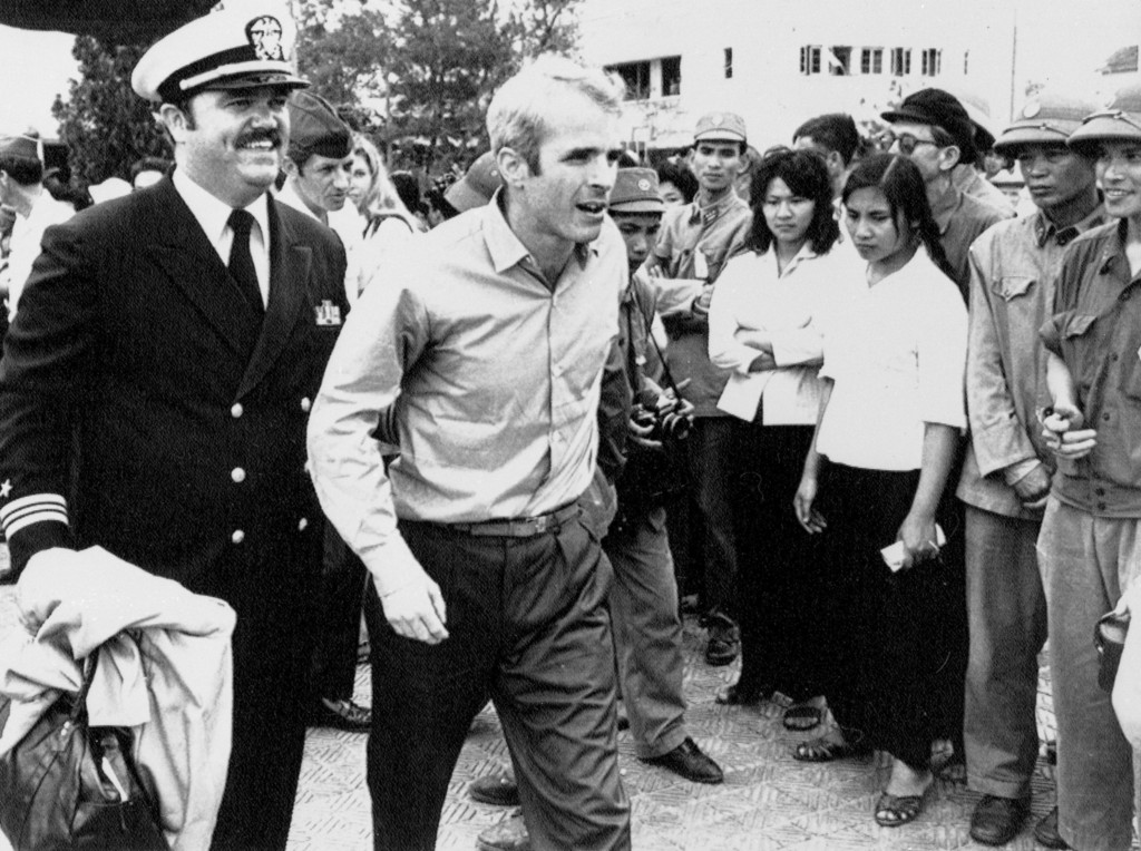 FILE - In this March 14, 1973, file photo, U.S. Navy Lt. Cmdr. John McCain, center, is escorted by Lt. Cmdr. Jay Coupe Jr., to Hanoi, Vietnam's Gia La