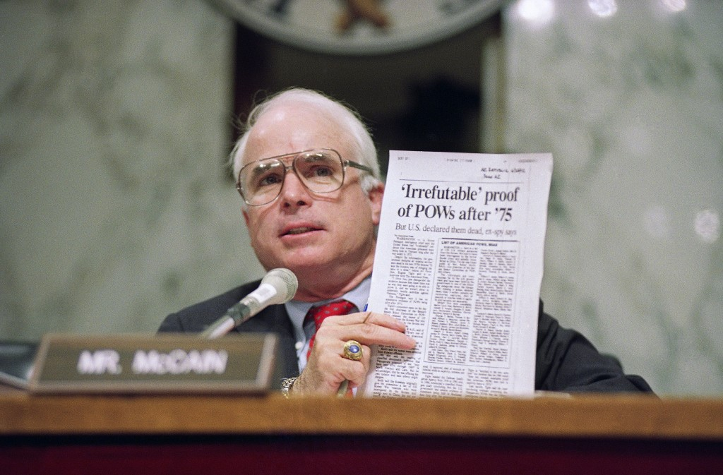 FILE - In this June 24, 1992, file photo, Sen. John McCain, R-Ariz., holds up an article from the Washington Times during a hearing of the Senate Sele