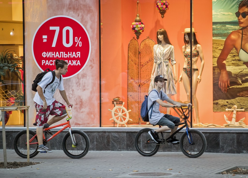 In this picture taken on Wednesday, Aug. 22, 2018, youngsters ride past a sign written in Russian, that advertises price cuts in Chisinau, Moldova.  R...