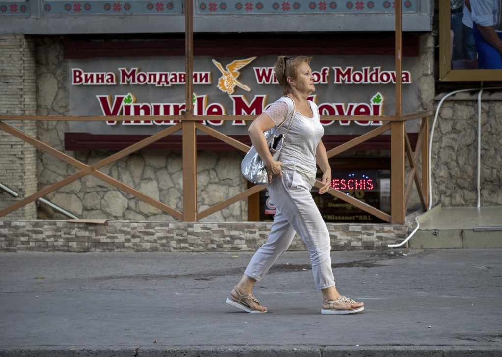 """In this picture taken on Wednesday, Aug. 22, 2018, a woman walks by a bilingual Romanian-Russian advert that reads """"The Wines of Moldova"""" in Chisinau,..."""