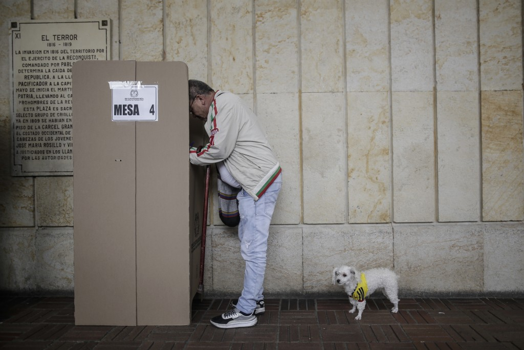 A man marks his ballot as his dog waits behind him during a nationwide referendum that seeks to curb corruption in Bogota, Colombia, Sunday, Aug. 26, ...