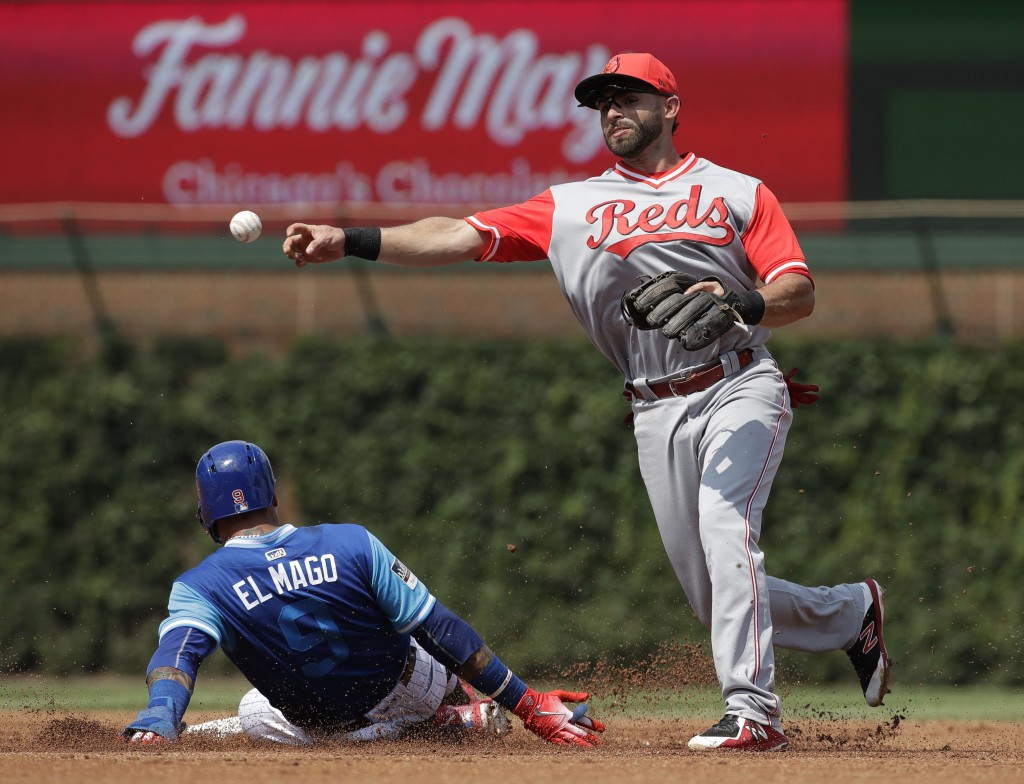 Cincinnati Reds shortstop Jose Peraza, right, throws to first after forcing out Chicago Cubs' Javier Baez at second during the first inning of a baseb...