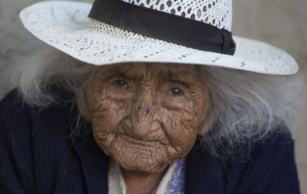 Julia Flores Colque eyes the camera while sitting outside her home in Sacaba, Bolivia, Thursday, Aug. 23, 2018. Her national identity card says Flores...