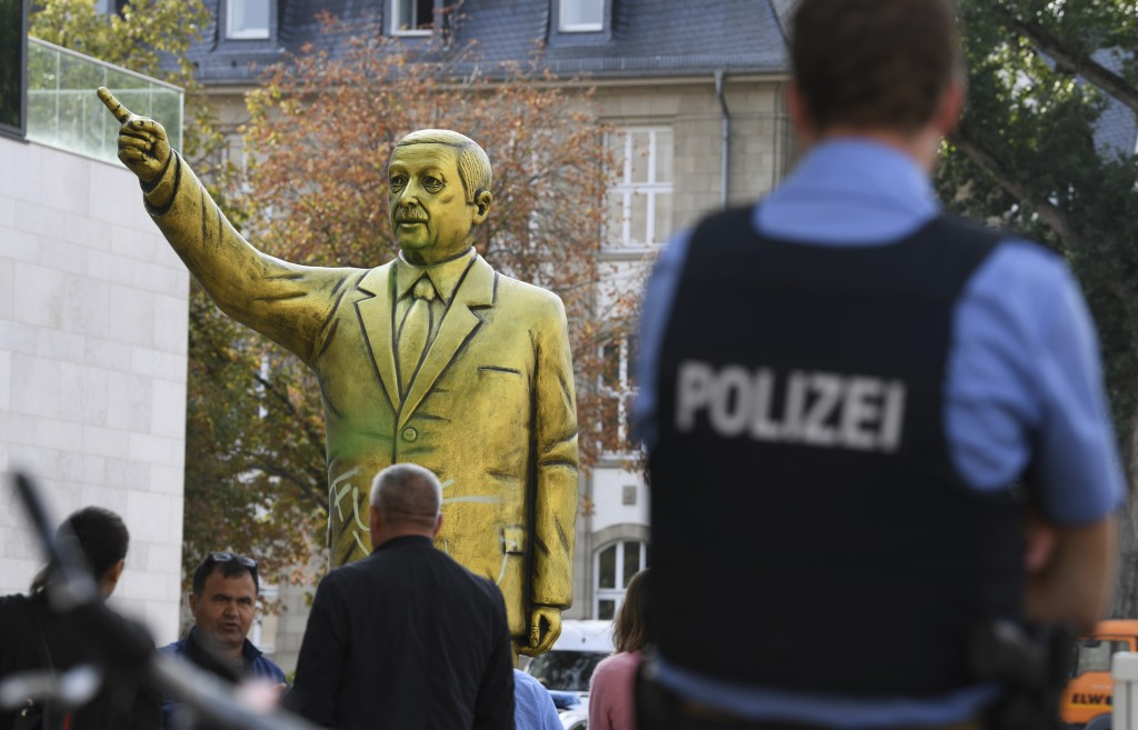 Police and passersby surround a statue showing Turkish President Erdogan which is part of the art festival  'Wiesbaden Biennale' in Wiesbaden, western