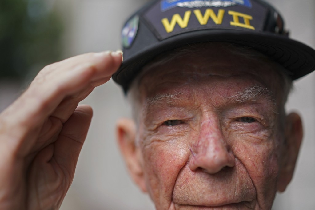 Lester Hollenback, of Deltona, Fla., left, a surviving member of the famed WWII Army unit Merrill's Marauders, salutes for a portrait during a gatheri
