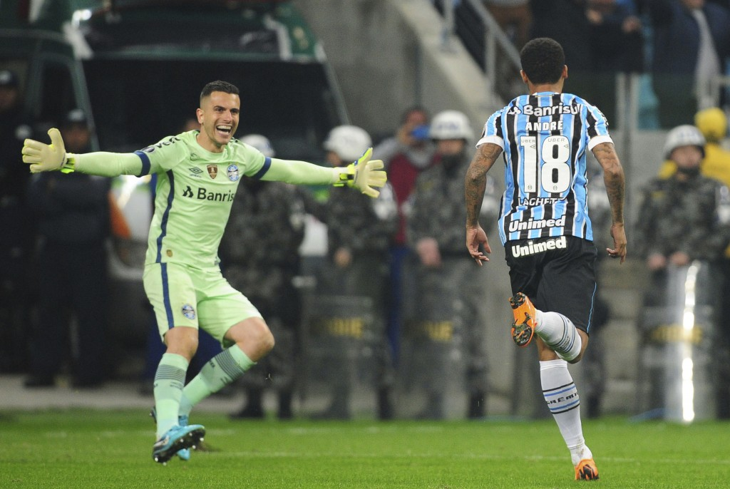 Andre of Brazil's Gremio, right, celebrates with goalkeeper Marcelo Grohe, after scoring from the penalty spot the victory goal against Argentina's Es...