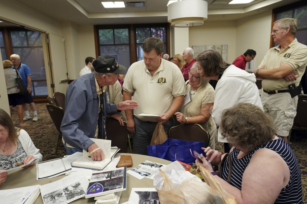 Lester Hollenback, of Deltona, Fla., left, a surviving member of the famed WWII Army unit Merrill's Marauders, talks with visitors as they look over m