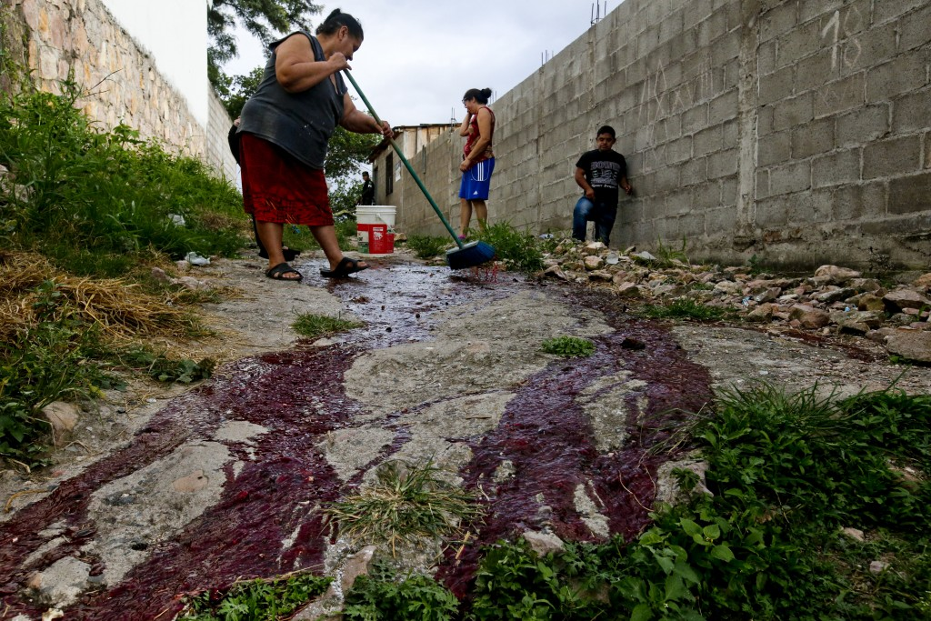 Family members of slain Ronald Blanco clean his blood from the alleyway of the Japon neighborhood where the Barrio 18 gang operates Tegucigalpa, Hondu...
