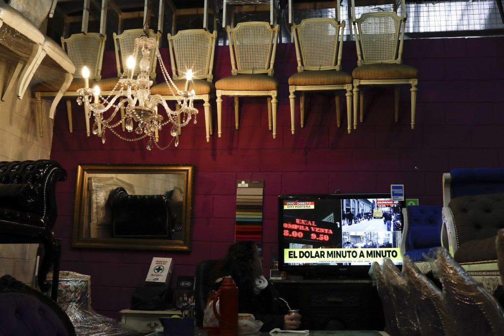 A woman watches news regarding U.S. dollar rates in Buenos Aires, Argentina, Thursday, Aug. 30, 2018. Argentina's Central Bank on Thursday increased i...