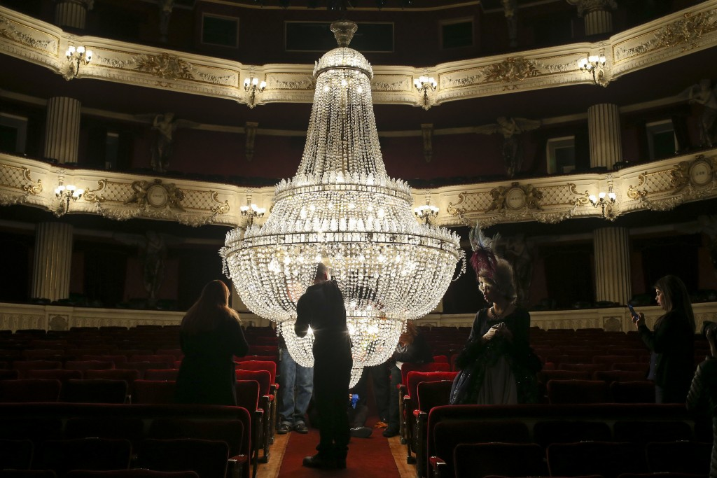 An actress in costume gives tourists a tour of the Municipal Theatre of Santiago as a worker cleans the chandelier in Santiago, Chile, Thursday, Aug. ...