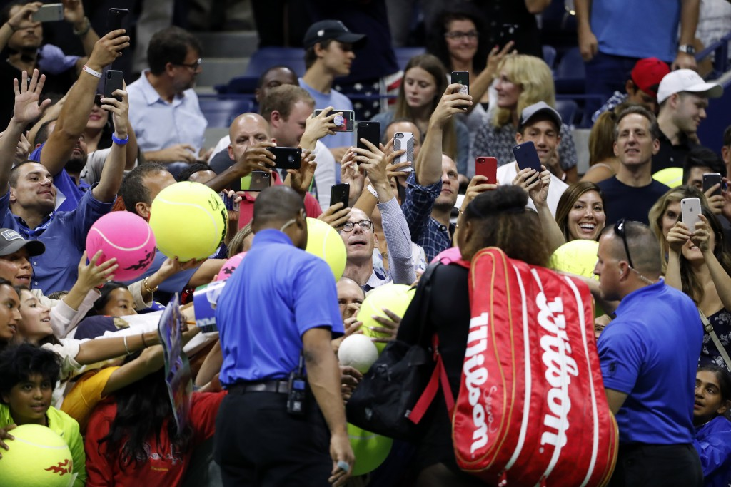Fans reach take photos id and ask for autographs from Serena Williams after she defeated her sister Venus Williams 6-1, 6-2 during the third round of ...