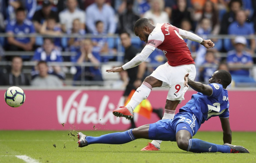 Arsenal's Alexandre Lacazette, top, scores his side's third goal during a Premier League soccer match between Cardiff City and Arsenal, at the Cardiff...