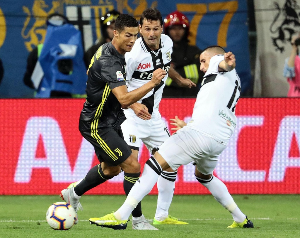 Juventus' Cristiano Ronaldo, left, is challenged by Parma's Antonino Barilla', right, and Massimo Gobbi during the Serie A soccer match between Parma