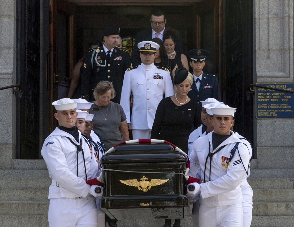 In this image provided by the U.S. Navy, Navy Body Bearers walk with the casket of Sen. John McCain, R-Ariz., followed by family members including Cin