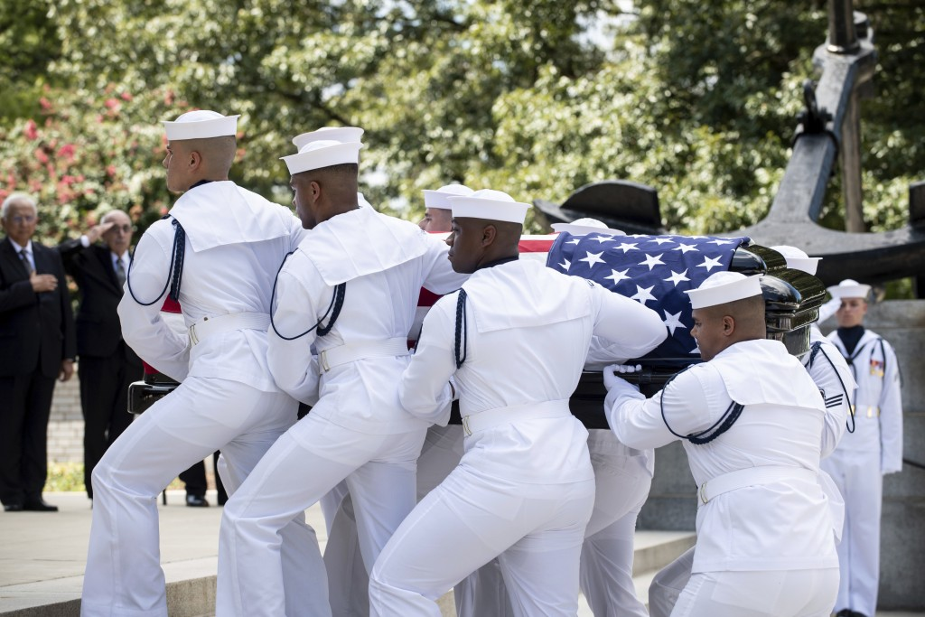 In this image provided by the U.S. Navy, Navy Body Bearers move the casket of Sen. John McCain, R-Ariz., from his processional hearse into the United