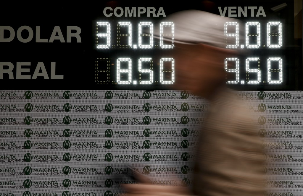 A man walks past a sign announcing the price of U.S. dollar and Brazilian real, in exchange for Argentine pesos, at an exchange house in Buenos Aires,