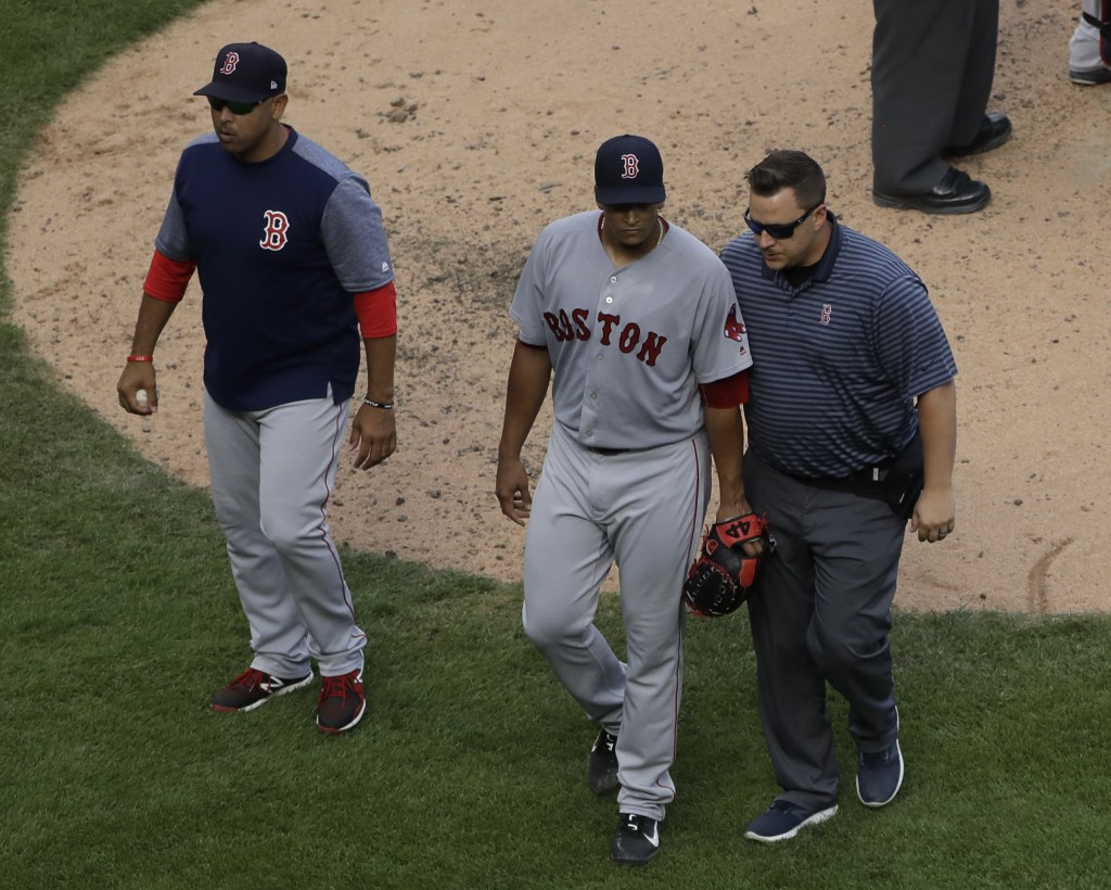 Boston Red Sox relief pitcher William Cuevas, center, leaves with a team trainer and manager Alex Cora, left, after an injury in the sixth inning of a...
