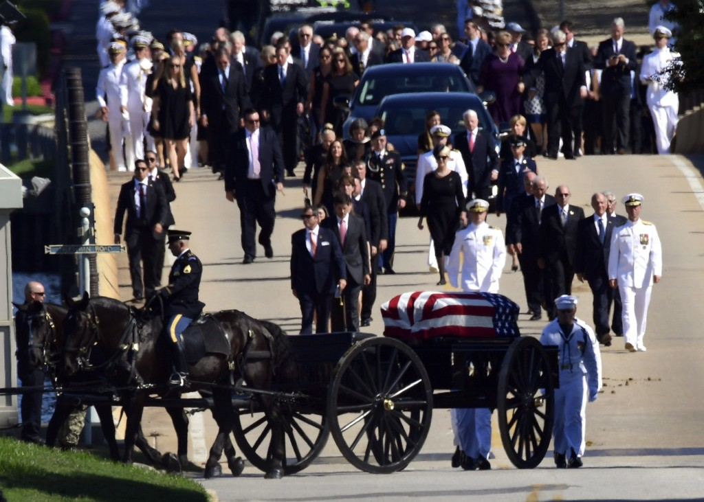 Family members, including Cindy McCain, back center, follow a horse-drawn caisson that carries the casket of Sen. John McCain, R-Ariz., as it proceeds