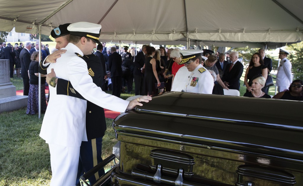 In this image provided by the family of John McCain, Jimmy McCain hugs his brother Jack McCain, touching casket, as Cindy McCain, watches during a bur