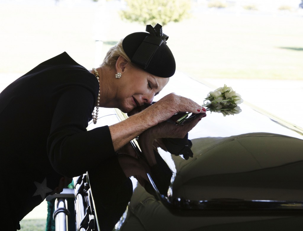 In this photo provided by the family of John McCain, Cindy McCain lays her head on the casket of Sen. John McCain, R-Ariz., during a burial service at