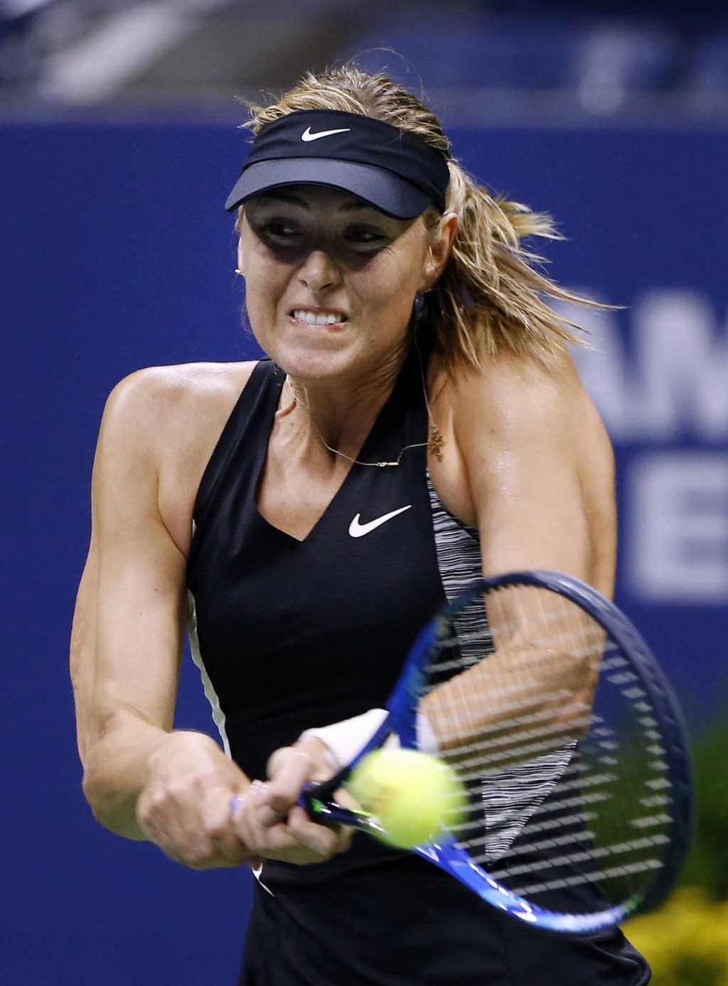 Maria Sharapova, of Russia, returns a shot to Carla Suarez Navarro, of Spain, during the fourth round of the U.S. Open tennis tournament, Monday, Sept...