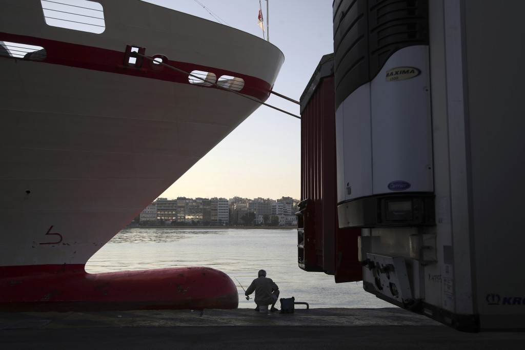 A man fishes between a docked ferry and parked truck containers during the second day of seamen's union's strike at a port of Piraeus, near Athens, Tu...