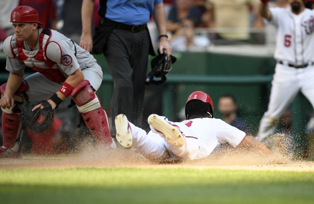 Washington Nationals' Michael Taylor slides home to score the game-winning run on a sacrifice fly by Bryce Harper during the tenth inning of a basebal...