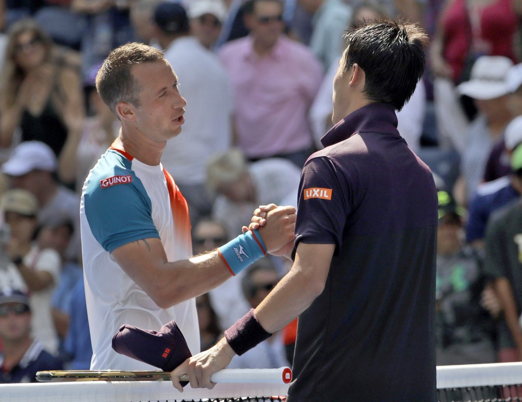Kei Nishikori, right, of Japan, shakes hands with Philipp Kohlschreiber, of Germany, after Nishikori defeated Kohlschreiber during the fourth round of...