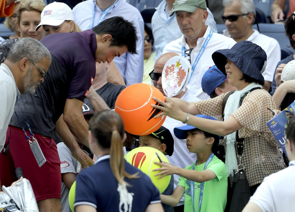 Kei Nishikori, of Japan, signs autographs for fans after defeating Philipp Kohlschreiber, of Germany, during the fourth round of the U.S. Open tennis ...