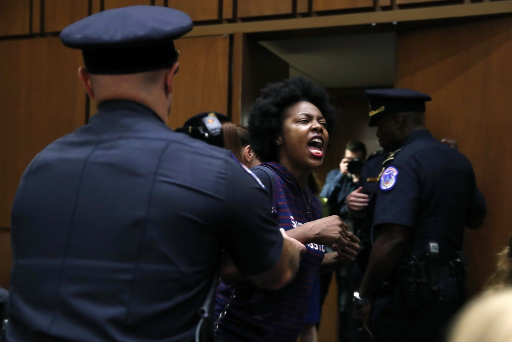 A protester against Supreme Court nominee Brett Kavanaugh is removed from his Senate Judiciary Committee confirmation hearing, on Capitol Hill, Tuesda...