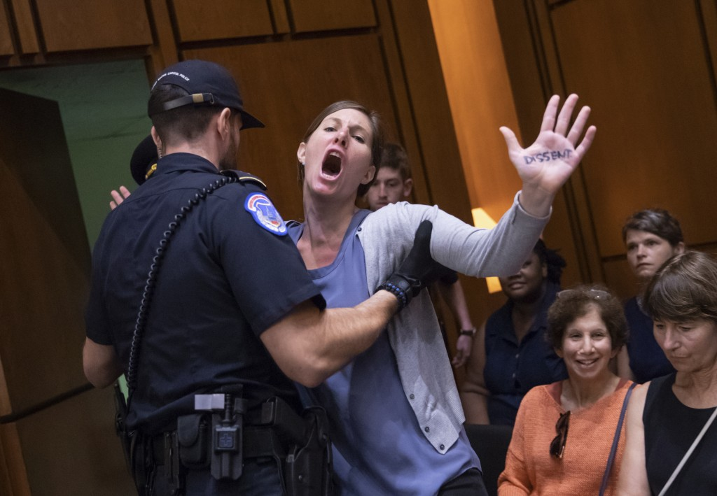A protester disrupts the proceedings as President Donald Trump's Supreme Court nominee, Brett Kavanaugh, appears before the Senate Judiciary Committee...