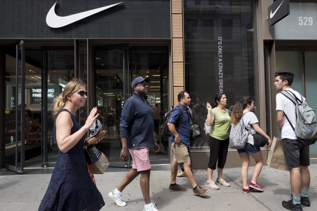 People pass a Nike store in New York, Tuesday, Sept. 4, 2018. An endorsement deal between Nike and Colin Kaepernick is prompting a flood of debate onl...