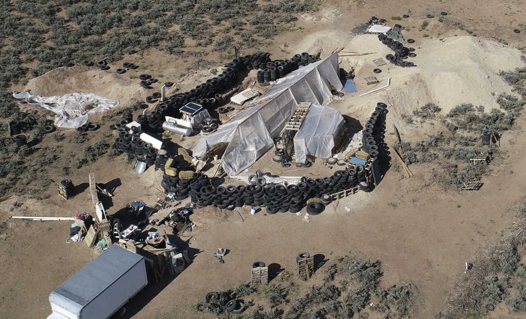 FILE - This Aug. 10, 2018, file photo shows a ramshackle compound in the desert area of Amalia, N.M. Five former residents of the compound in northern