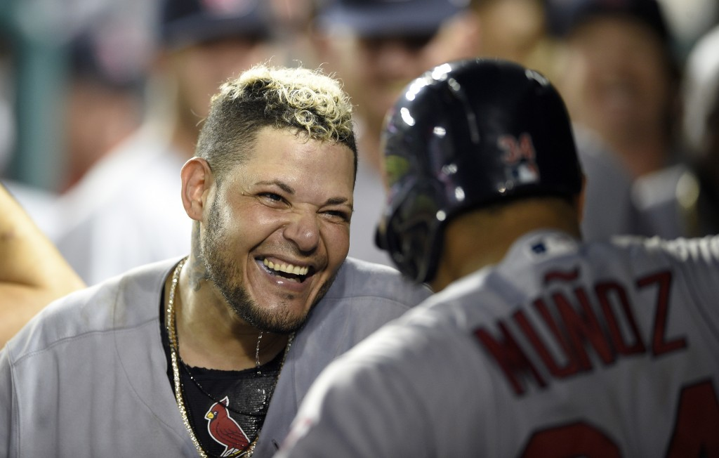 St. Louis Cardinals' Yadier Molina, left, celebrates his grand slam with Yairo Munoz, right, in the dugout during the ninth inning of a baseball game