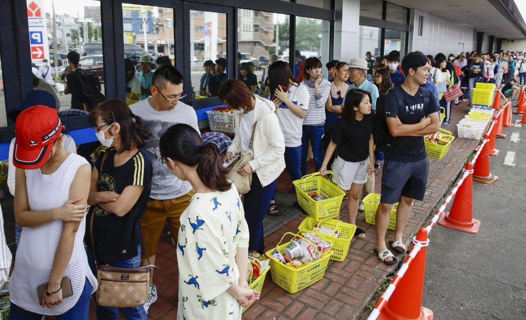 People wait in a long line to buy foods at a store in Sapporo, Hokkaido, northern Japan Thursday, Sept. 6, 2018. Rescuers were rushing to unearth surv