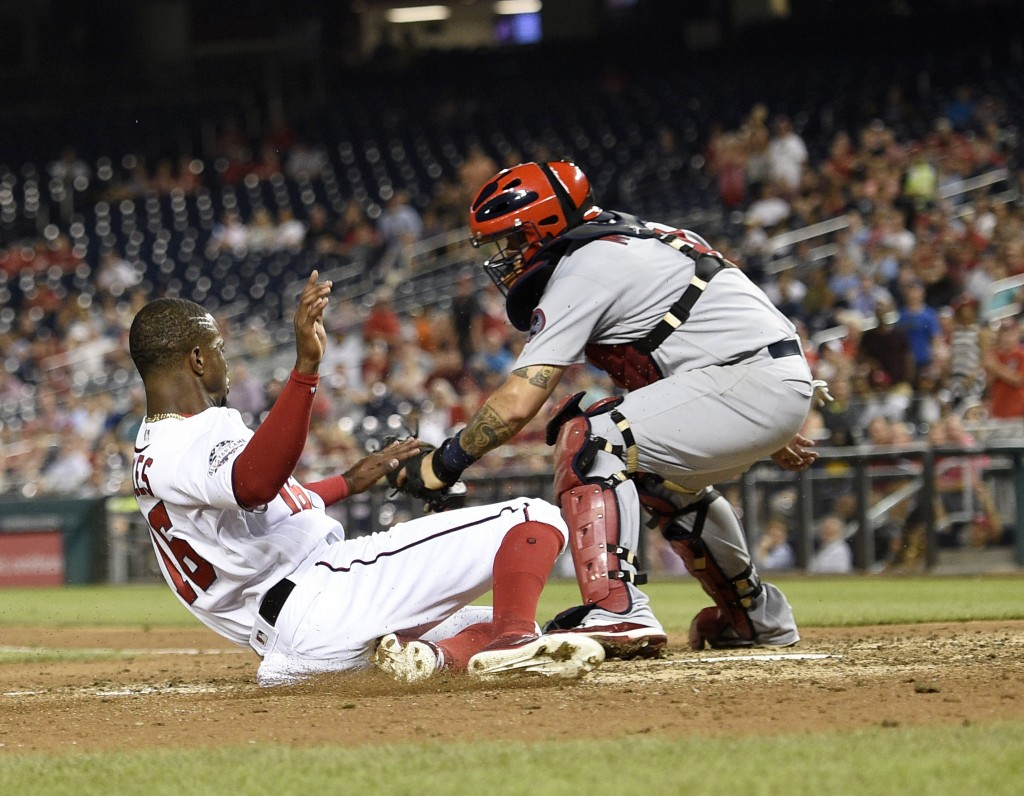 Washington Nationals' Victor Robles, left, slides home to score against St. Louis Cardinals catcher Yadier Molina, right, during the fifth inning of a