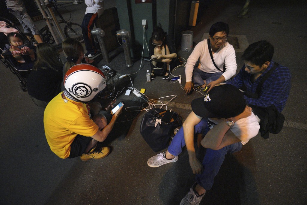 People gather to charge their mobile phones in the blackout on the center of Sapporo city, Hokkaido, northern Japan, Thursday, Sept. 6, 2018. A powerf