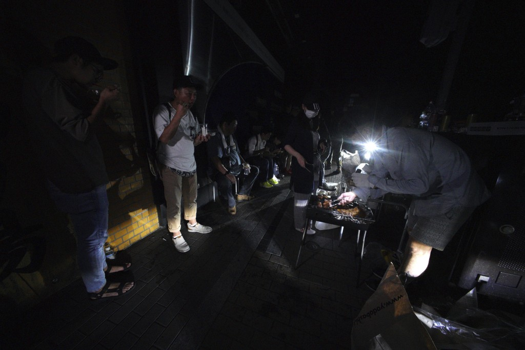 People gather to cook and serve to neighbors in the blackout on the center of Sapporo city, Hokkaido, northern Japan, Thursday, Sept. 6, 2018. A power