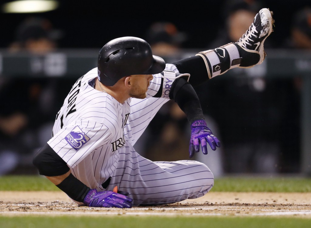 Colorado Rockies' Trevor Story falls in the batter's box after connecting for a solo home run off San Francisco Giants starting pitcher Andrew Suarez ...