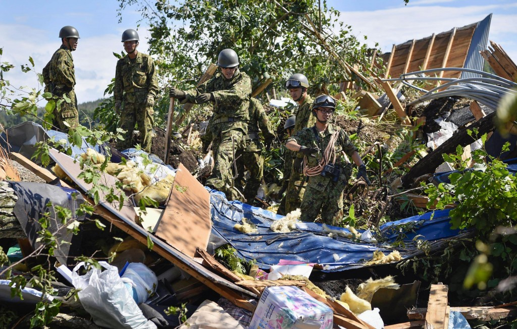 Japan Ground Self-Defense Force personnel search for missing persons at the site of a landslide triggered by a powerful earthquake in Atsuma town, Hok