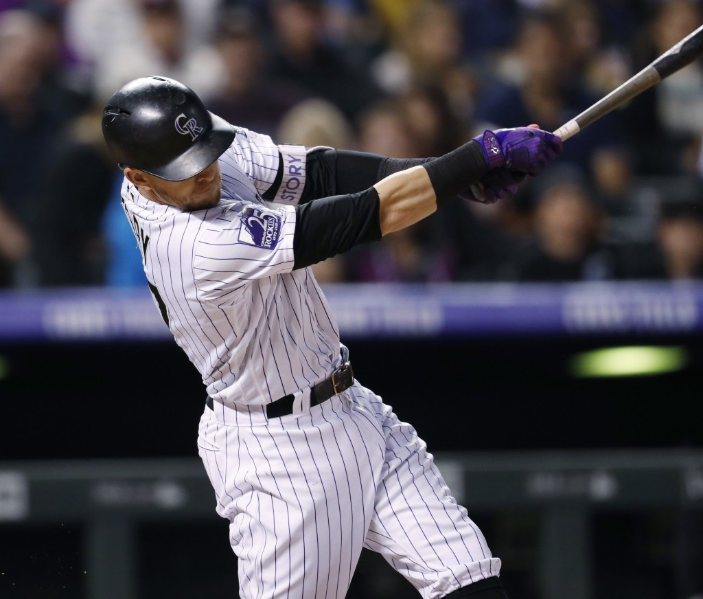 Colorado Rockies' Trevor Story follows through on a solo home run off San Francisco Giants starting pitcher Andrew Suarez during the sixth inning of a...