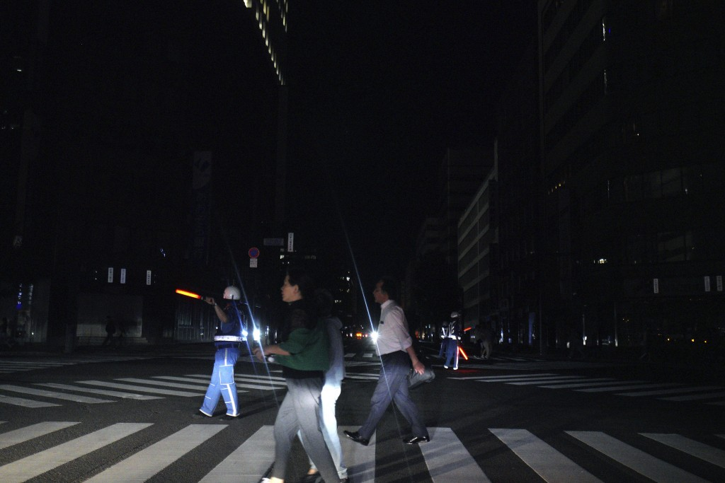 Police officers guide traffic as pedestrian walk in the blackout on the center of Sapporo city, Hokkaido, northern Japan, Thursday, Sept. 6, 2018. A p...