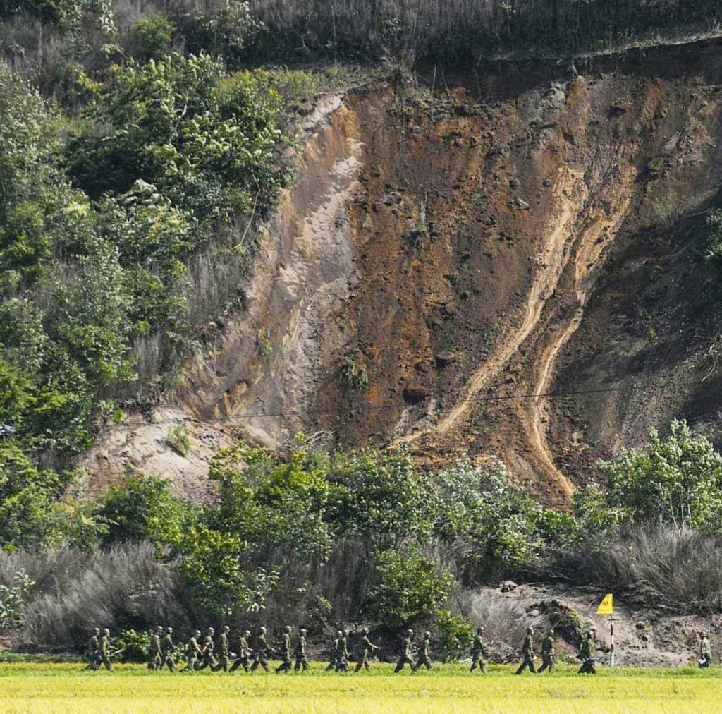 Japan Ground Self-Defense Force personnel head to the site of a landslide following a strong earthquake in Atsuma town, Hokkaido, northern Japan, Thur