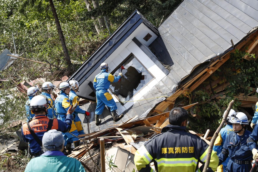 Police, in blue with yellow uniform, search for missing persons around a house destroyed by a landslide after a powerful earthquake in Atsuma town, Ho