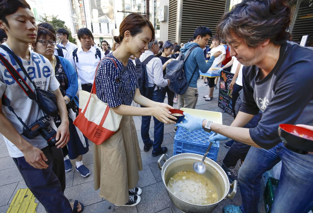 A worker of a restaurant near the area distributes soup following a powerful earthquake in Sapporo, Hokkaido, northern Japan Thursday, Sept. 6, 2018.