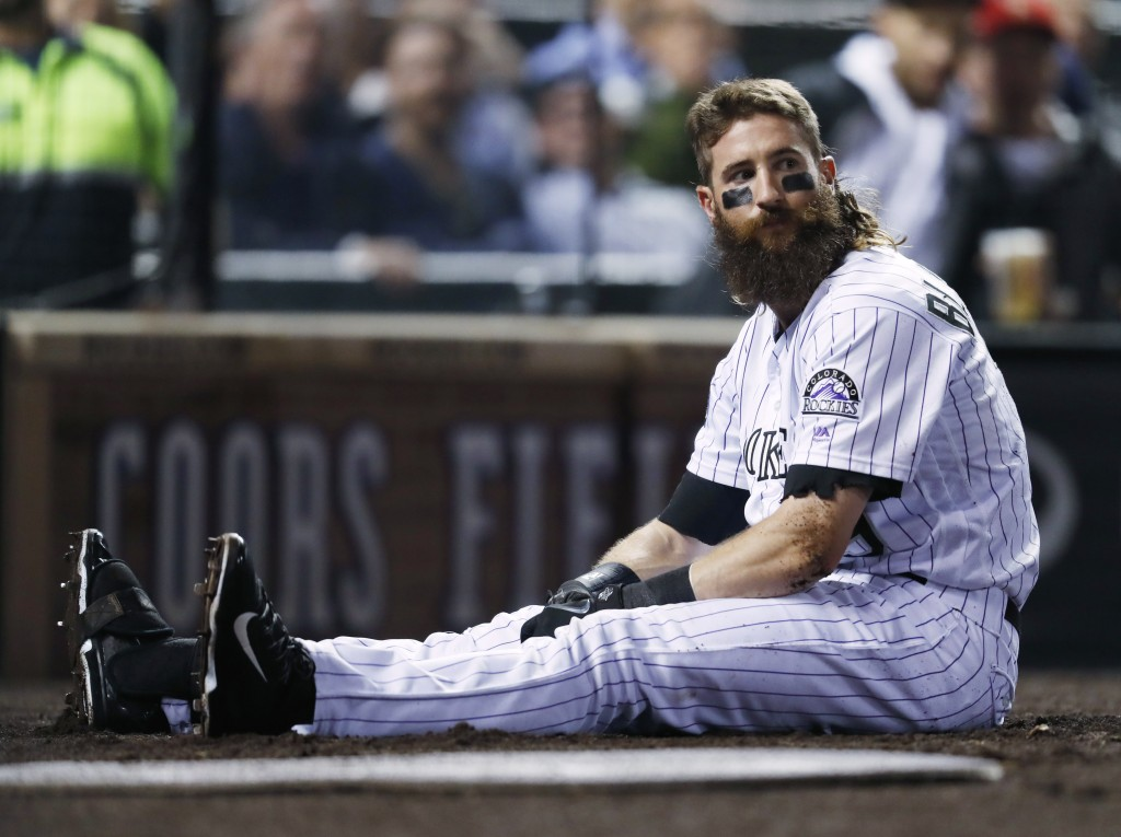 Colorado Rockies' Charlie Blackmon ends up sitting in the on-deck circle after taking a foul ball hit by Antonio Senzatela off the batting helmet in t...