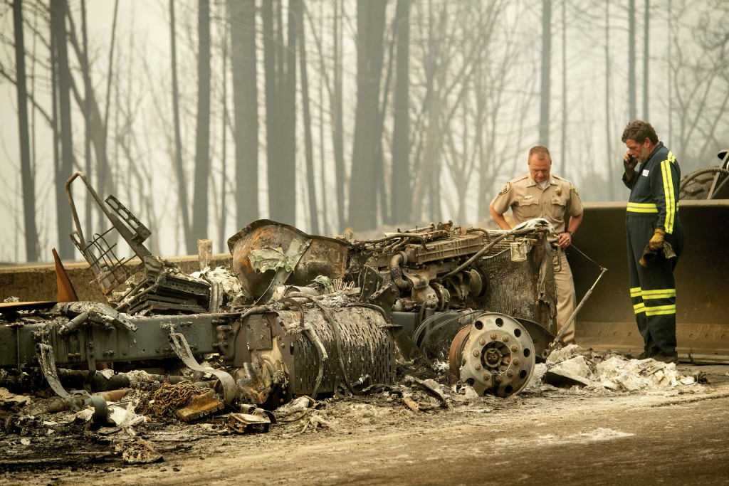 California Capt. Mark Loveless examines a truck scorched by the Delta Fire burning along Interstate 5 in the Shasta-Trinity National Forest, Calif., o